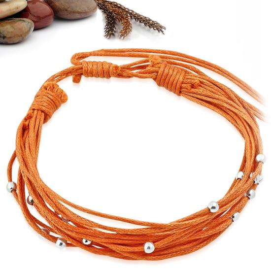 Narancs sárga színű szövet karkötő, fém dísszel